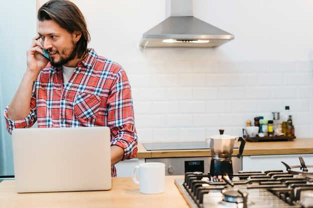 Un hombre joven que habla en el teléfono móvil con la taza del café y el portátil en el mostrador de la cocina