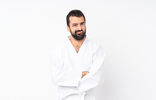Hombre joven que hace karate sobre la sensación blanca aislada molesta