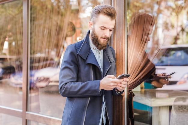 Hombre joven que se inclina en la ventana de cristal usando el teléfono celular