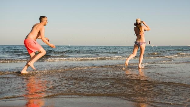 Hombre joven que lanza el chapoteo del agua sobre su novia cerca del mar en la playa