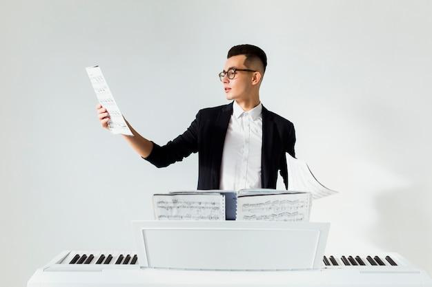 Hombre joven que lee la hoja musical que está parada detrás del piano contra el fondo blanco