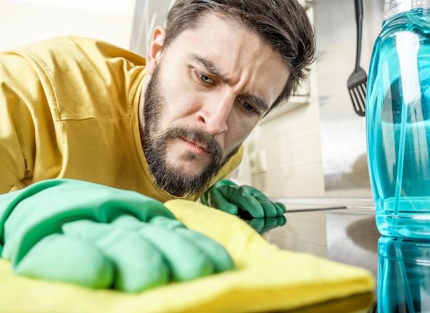 Hombre joven que limpia la cocina moderna