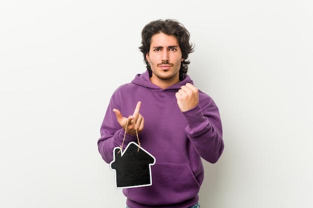 Hombre joven que lleva a cabo una forma del icono de la casa que muestra el puño a la cámara, expresión facial agresiva.