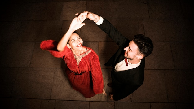 Hombre joven que lleva a cabo la mano de bailar a la mujer feliz encantadora