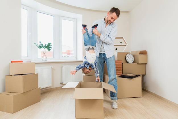 Hombre joven que lleva a su hijo del niño al revés debajo de la caja de cartón en el nuevo hogar