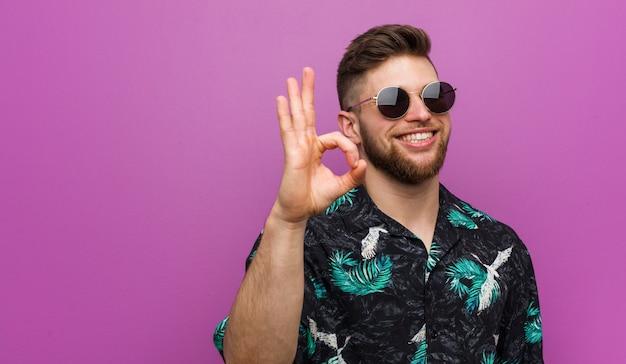 El hombre joven que lleva vacaciones mira alegre y confiado que muestra gesto aceptable.