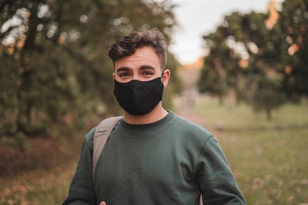 Hombre joven que llevaba una mascarilla en un parque
