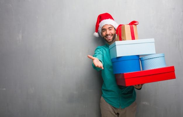 Hombre joven que llevaba un sombrero de santa con regalos para saludar a alguien