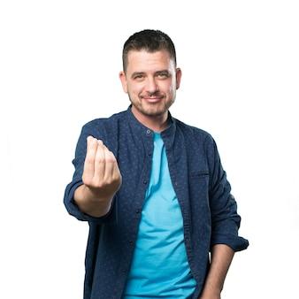 El hombre joven que llevaba un traje azul. haciendo el gesto de dinero.