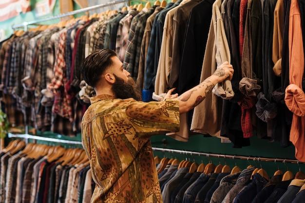 Hombre joven que mira la camisa que cuelga en el carril dentro de la tienda de ropa