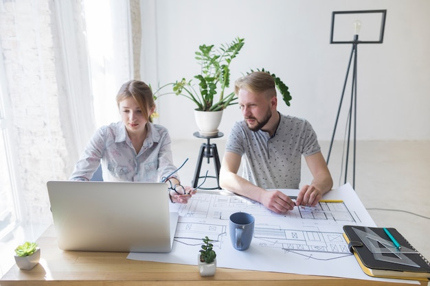 Hombre joven que mira la computadora portátil usando a su colega en el lugar de trabajo