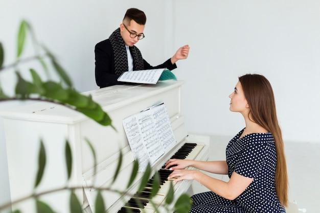Hombre joven que mira la hoja musical que ayuda a la mujer que toca el piano