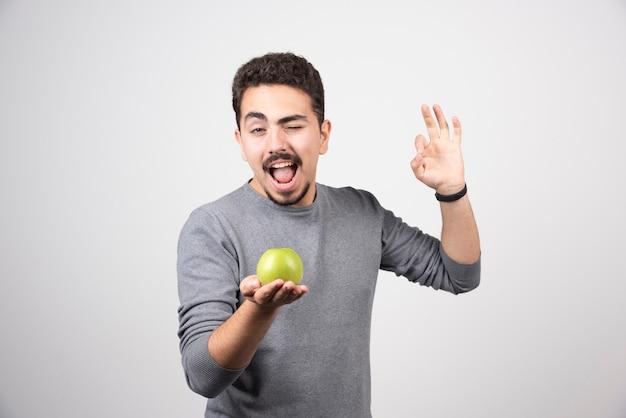Hombre joven que mira la manzana verde felizmente.