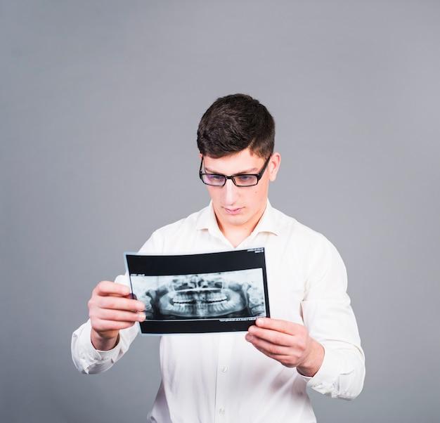 Hombre joven que mira la radiografía de los dientes