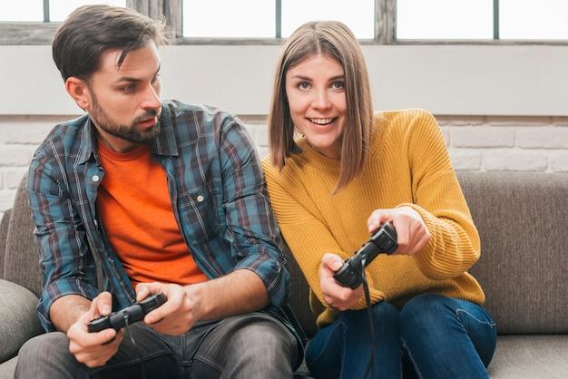 Hombre joven que mira a su novia que juega al videojuego con la palanca de mando