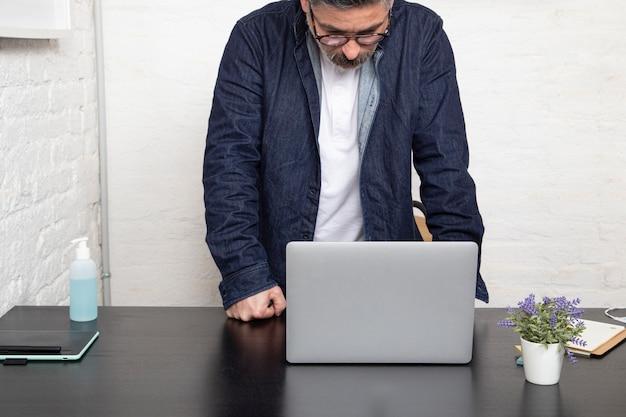 Hombre joven que mira su su computadora portátil en casa. concepto de trabajo en casa.