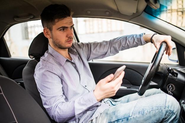 Hombre joven que mira el teléfono móvil mientras conduce un automóvil.