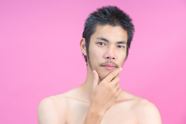 Hombre joven que muestra la cara sin maquillaje en el rosa.