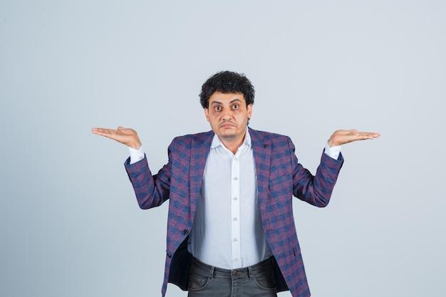 Hombre joven que muestra un gesto de impotencia en camisa, chaqueta, pantalón y parece confundido. vista frontal.