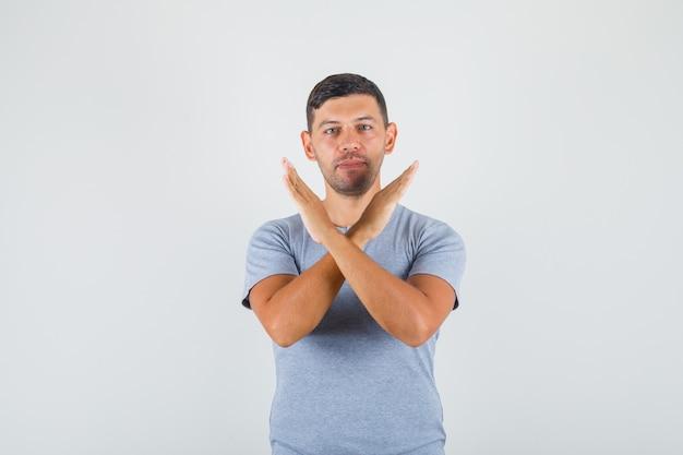 Hombre joven que muestra el gesto de la parada con las manos cruzadas en la camiseta gris y que parece confiado.