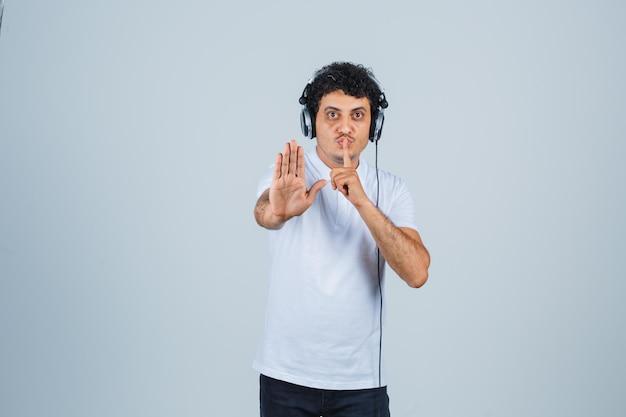 Hombre joven que muestra el gesto de la parada con el signo de silencio en la camiseta blanca y que parece sensato. vista frontal.