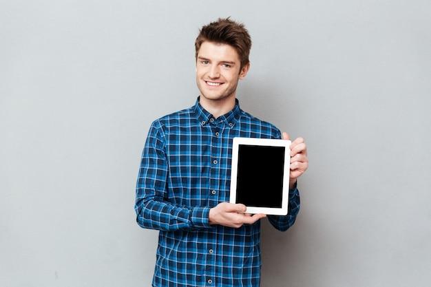 Hombre joven que muestra la pantalla en blanco de la tableta aislada