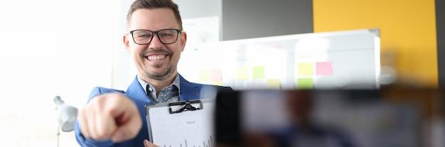 Hombre joven que muestra la pantalla del teléfono móvil con el concepto de formación empresarial de dedo
