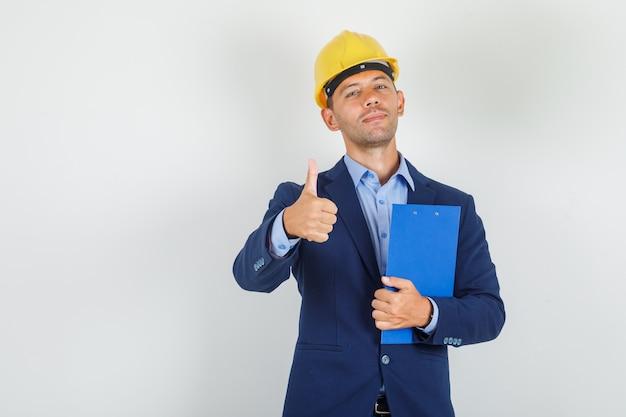 Hombre joven que muestra el pulgar hacia arriba con el portapapeles en traje, casco de seguridad y mirando complacido.