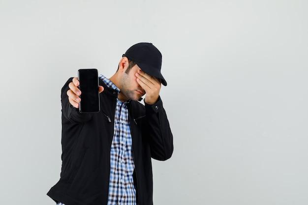 Hombre joven que muestra el teléfono móvil, sosteniendo la mano en los ojos en camisa, chaqueta, gorra, vista frontal.