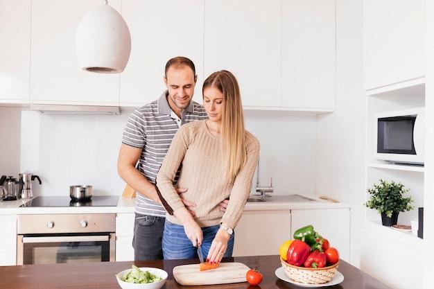 Hombre joven que está parado detrás de su esposa que corta la zanahoria con el cuchillo en la tajadera