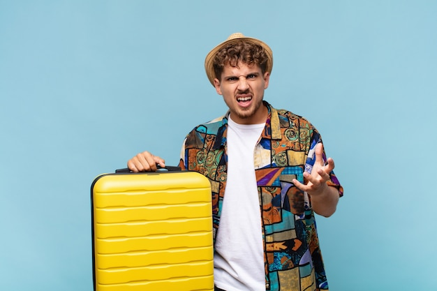 Hombre joven que parece enojado, molesto y frustrado gritando wtf. concepto de vacaciones