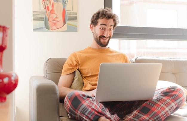 Hombre joven que parece feliz y gratamente sorprendido emocionado con una expresión fascinada y conmocionada