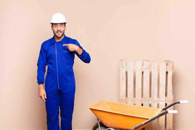 Hombre joven que parece feliz, orgulloso y sorprendido, apuntando alegremente a sí mismo, sintiéndose seguro y elevado concepto de construcción