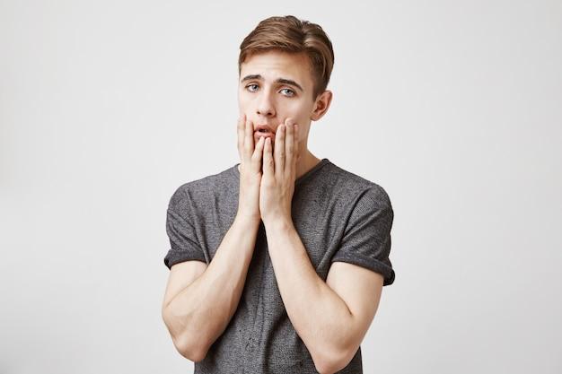 Hombre joven que parece triste y aburrido parado cerca de la pared.