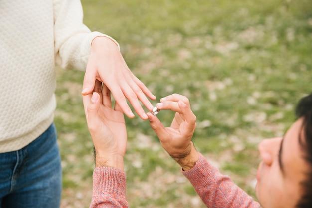 Hombre joven que pone el anillo de bodas en el dedo del amor