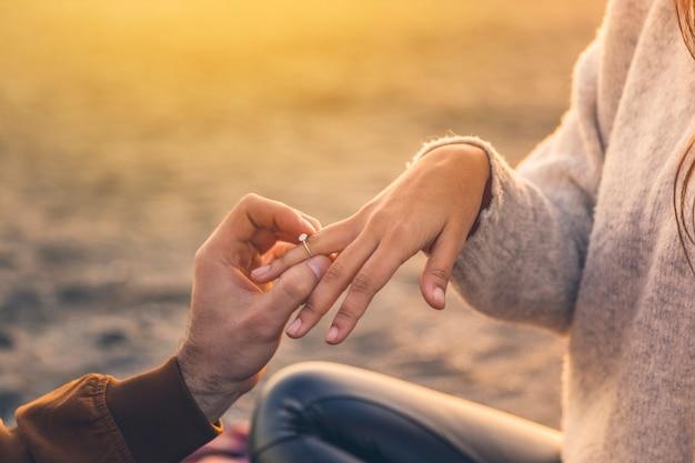 Hombre joven que pone el anillo de bodas en el dedo de la mujer