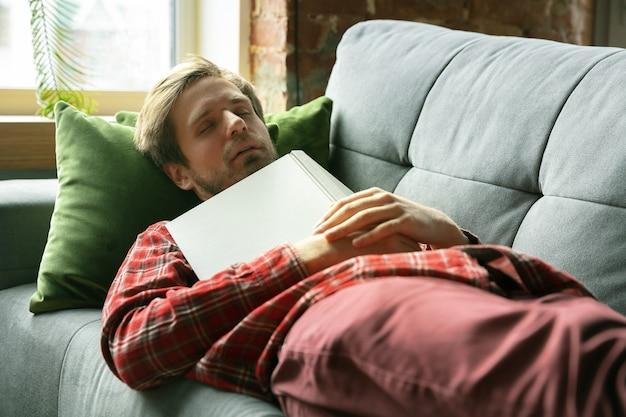 Hombre joven que se queda en casa en el sofá