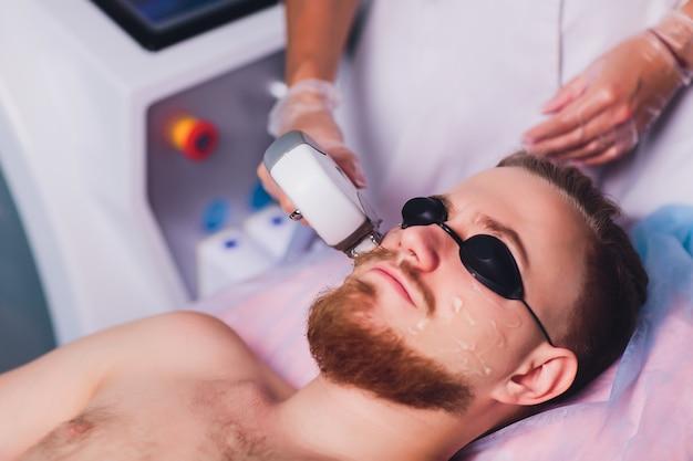 Hombre joven que recibe el tratamiento de depilación láser en el centro de belleza.
