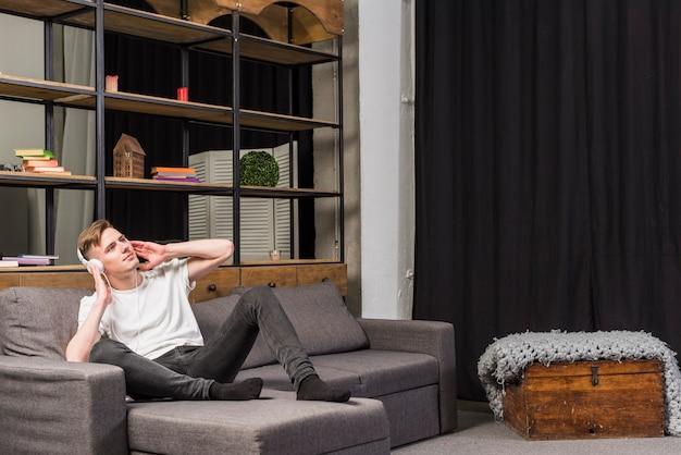 Hombre joven que se relaja en música que escucha del sofá en el auricular en casa