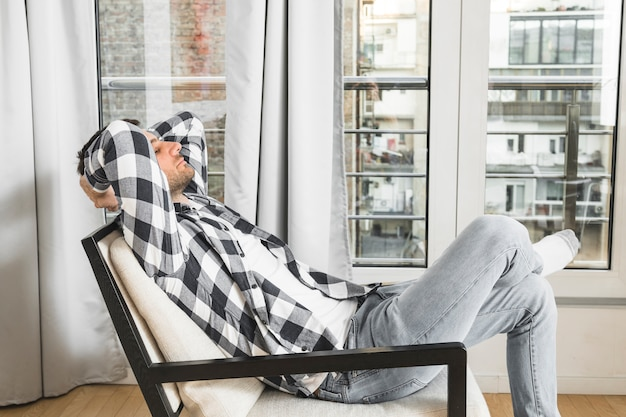 Hombre joven que se relaja en silla en casa