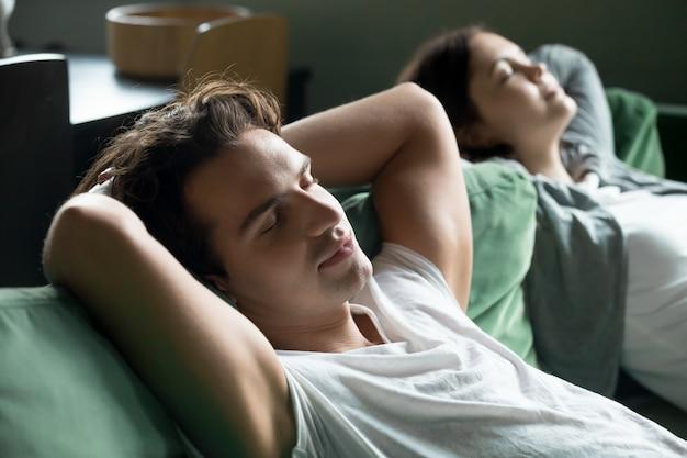 Hombre joven que se relaja en el sofá cómodo con la novia en casa