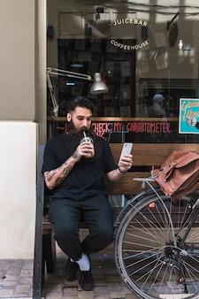 Hombre joven que se sienta en el banco que bebe el chocolate con leche que toma el selfie en el teléfono móvil