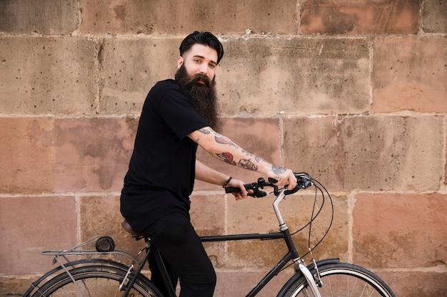 Hombre joven que se sienta en la bicicleta delante de la pared resistida