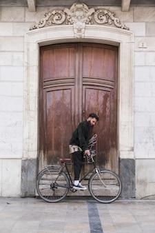 Hombre joven que se sienta en la bicicleta delante de la puerta de madera del vintage