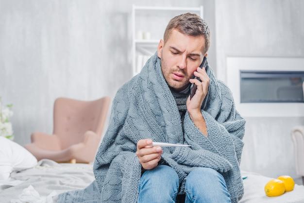 Hombre joven que se sienta en la cama envuelta en la bufanda que mira el termómetro que habla en el teléfono móvil