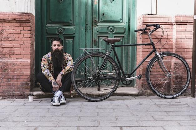 Hombre joven que se sienta cerca de la bicicleta con la taza de café para llevar delante de la pared verde de madera