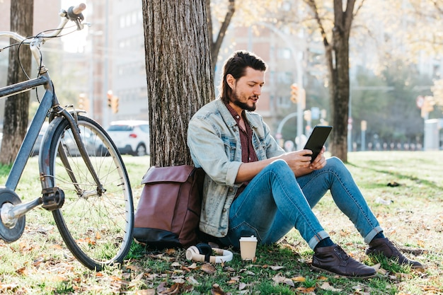 Hombre joven que se sienta debajo del árbol usando el teléfono móvil en el parque con la taza de papel del café para llevar