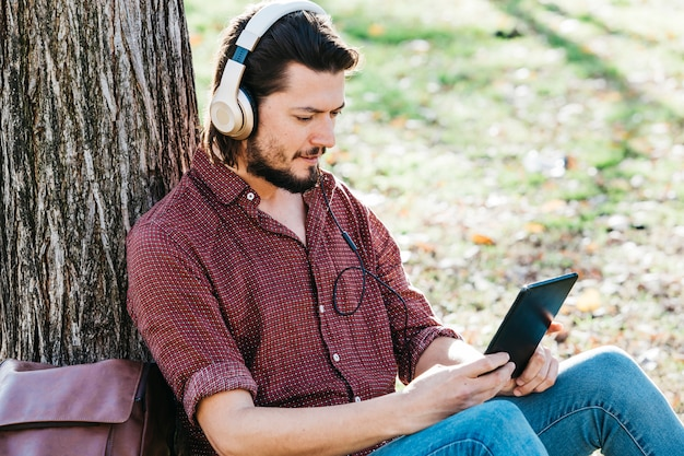 Hombre joven que se sienta debajo de la música que escucha del árbol en el auricular a través del teléfono móvil