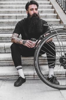Hombre joven que se sienta en la escalera que sostiene la taza de café disponible