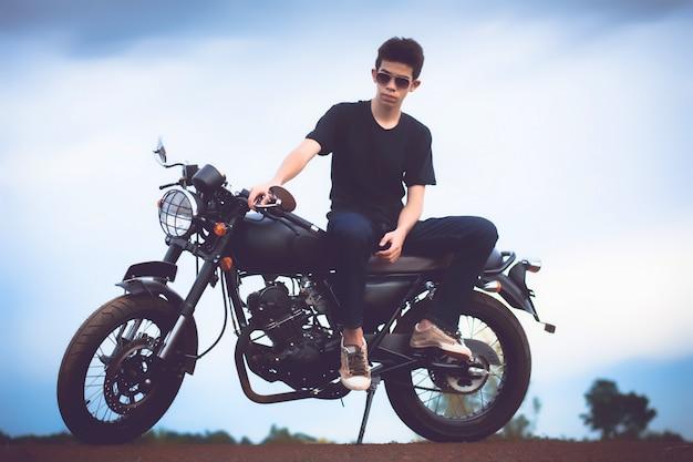 Hombre joven que se sienta con la moto al lado del lago natural y hermoso.